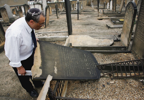 A caretaker inspects the damage in a Jewish cemetery in London, June 2005. (Photo by Graeme Robertson/Getty Images.)