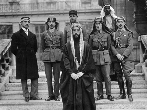 Emir Feisal's delegation at Versailles, during the Paris Peace Conference of 1919. Left to right: Rustum Haidar, Nuri as-Said, Prince Feisal, Captain Pisani (behind Feisal), T. E. Lawrence, Feisal's slave, Captain Hassan Khadri.