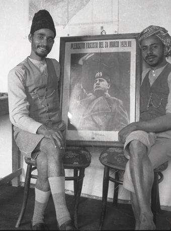 Haybi and an Arab cook pose with a poster of Mussolini.