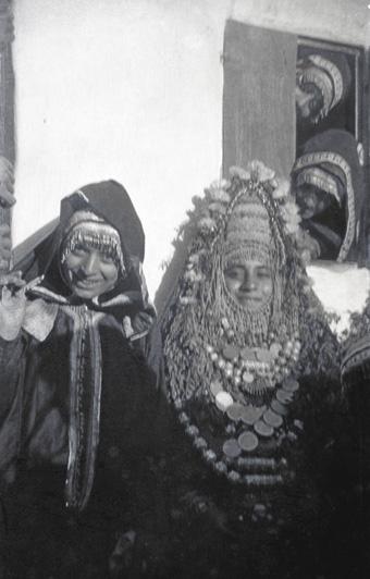 A smiling Jewish bride, right, in full wedding attire.