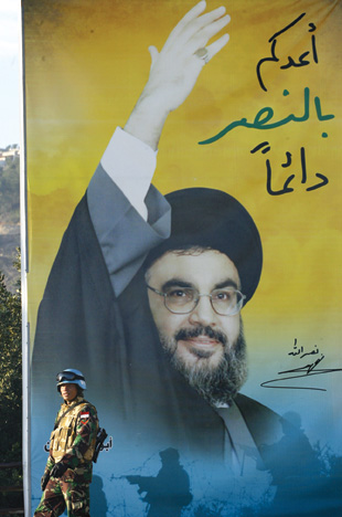 A peacekeeper of the United Nations Interim Force in Lebanon (UNIFIL) stands by a billboard with Hezbollah chief Hassan Nasrallah.