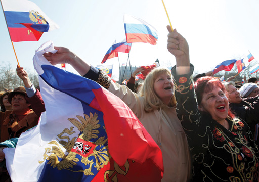 Supporters react as they watch the speech of Russian President Vladimir Putin on a screen in central Sevastopol, Crimea, Ukraine.