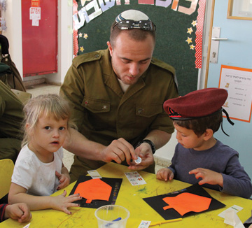 An Israeli soldier going through the conversion process visits a kindergarten in Efrat to learn about Hanukkah, November 2013. (Photo by Gershon Elinson/FLASH90.)