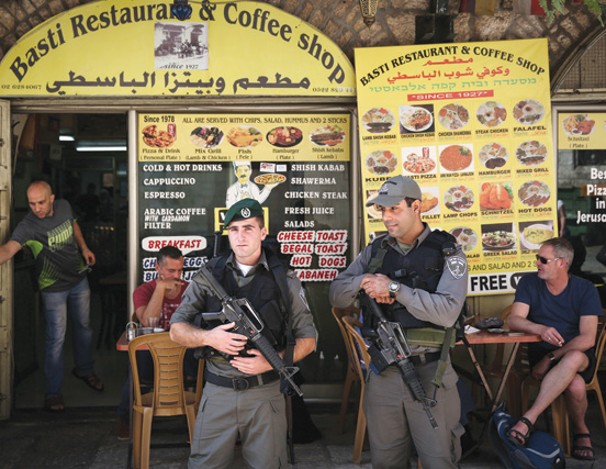 Israeli Border Police keep watch outside an Arab restaurant in Jerusalem's Old City. (Photo by Hadas Parush/Flash90.)