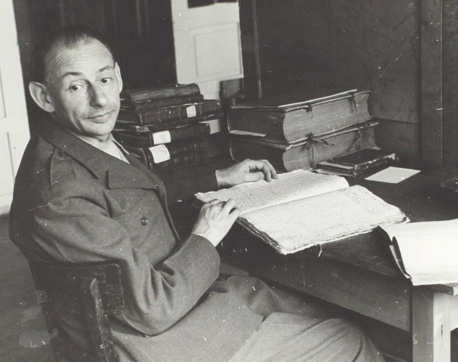 Gershom Scholem in Offenbach, Germany, 1946, identifying Hebrew manuscripts stolen by the Nazis. (Courtesy of the Gershom Scholem Archive, The National Library of Israel.)
