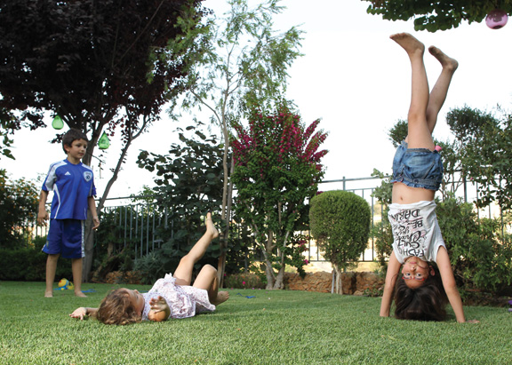 Israeli children play in a garden on a hot summer day. (Photo by Nati Shohat/FLASH90.)