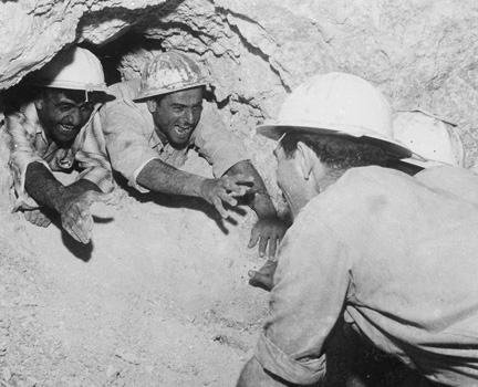 Excavation crews reach out to each other after tunneling through the rock as part of the National Water Carrier, 1960s, which carried billions of gallons of water to the Negev. (Courtesy of Daniel Rosenblum/Mekorot.)