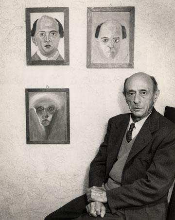 Arnold Schoenberg with some of his self-portraits, 1948. (Photo by Richard Fish, courtesy of  the Arnold Schoenberg Center, Vienna.)