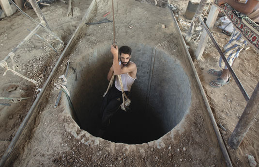 A Palestinian man is lowered into a smuggling tunnel beneath the Gaza-Egypt border, in the southern Gaza Strip, September 2013. (Photo by Mahmud Hams/AFP/Getty Images.)
