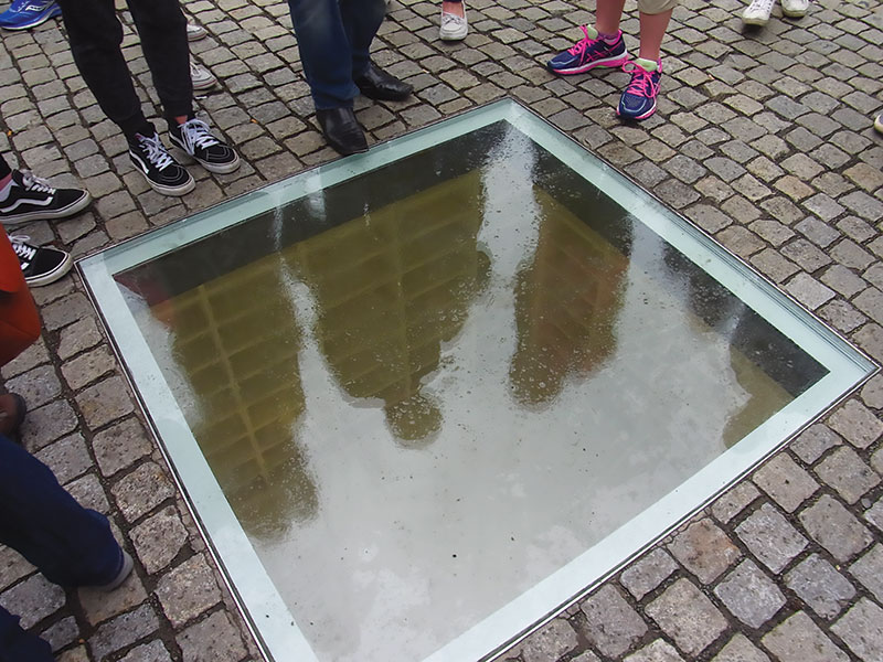 Photo of underground memorial consisting of a window on the surface of the plaza, under which vacant bookshelves are lit and visible.