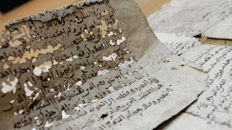 Photo of worn and disintegrating pages of manuscripts.