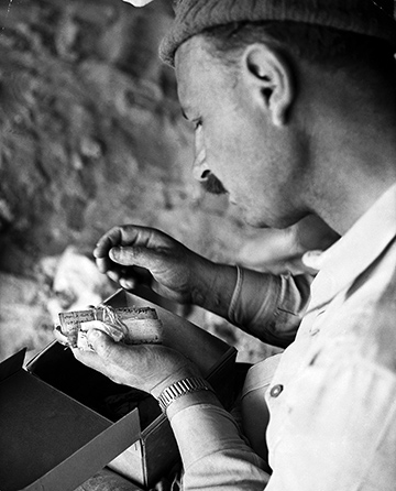 Photo of a man examining a bundle of papyri, which was found in a sheepskin bag in Israel.