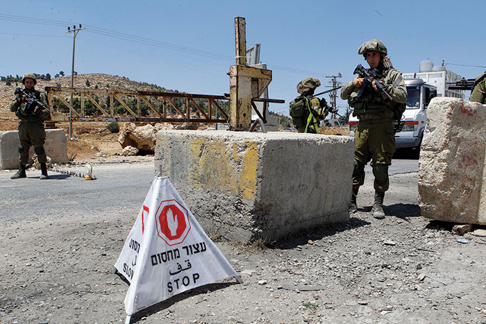 Photo of Israeli soldiers standing guard at a checkpoint.