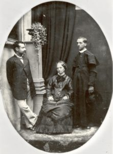 Black and white archival photo of a man in priest's robes standing next to a woman, seated, and a second man, standing.
