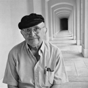 Photo contains a man wearing a hat and glasses