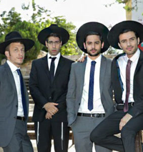 Image shows four young men wearing suits and fedoras.