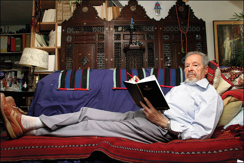 Photo of Albert Memmi at home sitting on a couch reading