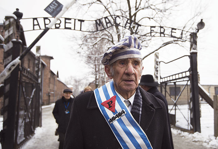 Auschwitz survivor stands in front of concentration camp gate.