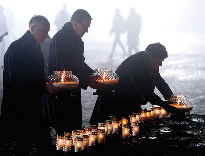 Political leaders lighting candles at the International Monument to the Victims of Fascism.