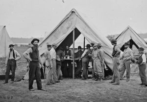 Black and white photo shows a group of men in and around a Civil War-era tent.