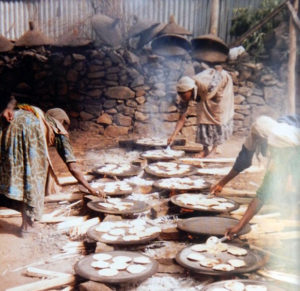 Image shows women preparing matza over open-hair cooking fires.