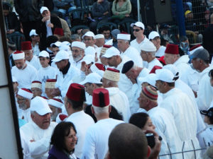Image shows a group of people wearing white clothing and red and white headgear.