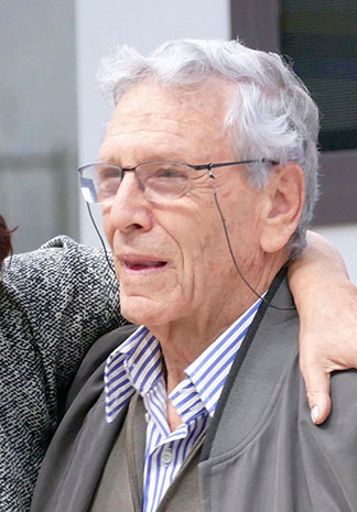 Photograph of Amos Oz in his older years, wearing glasses, looking away from the camera, someone's arm around his shoulder.