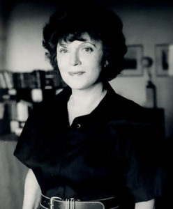 Black and white photo shows Muriel Spark smiling at the camera.