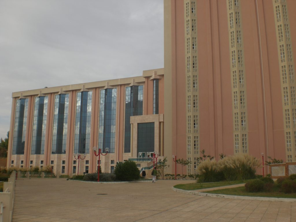 Photograph of the National Library of Tunisia, a large, red brick building with strong, vertical elements.