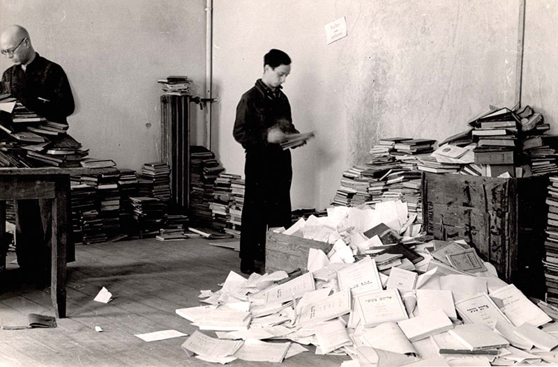 Photo of man sorting through piles of confiscated books