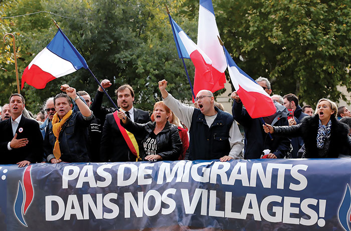 Photograph of a French demonstration with a large banner and flags