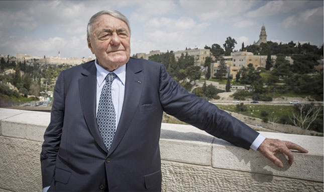 Photograph of a man in a suit leaning against a wall with Israel landscape in the background.