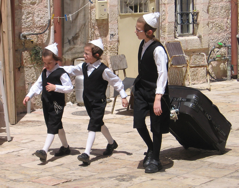 Three boys in black suits and white yarmulkes on a stone-lined street in Jerusalem.