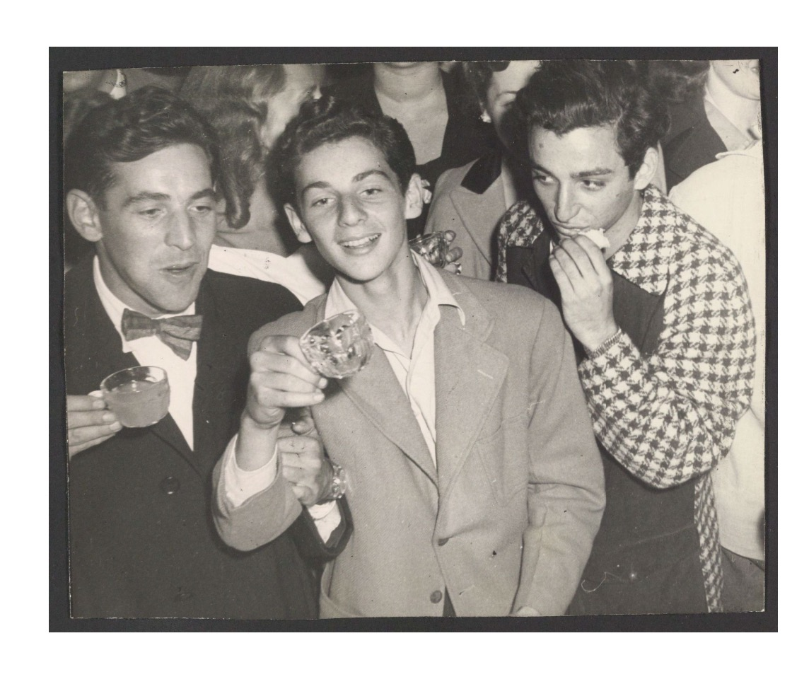 Black and white photograph of three young man drinking at a party.