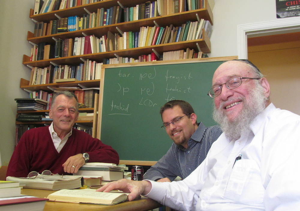 Three men at a classroom table, smiling for the camera.