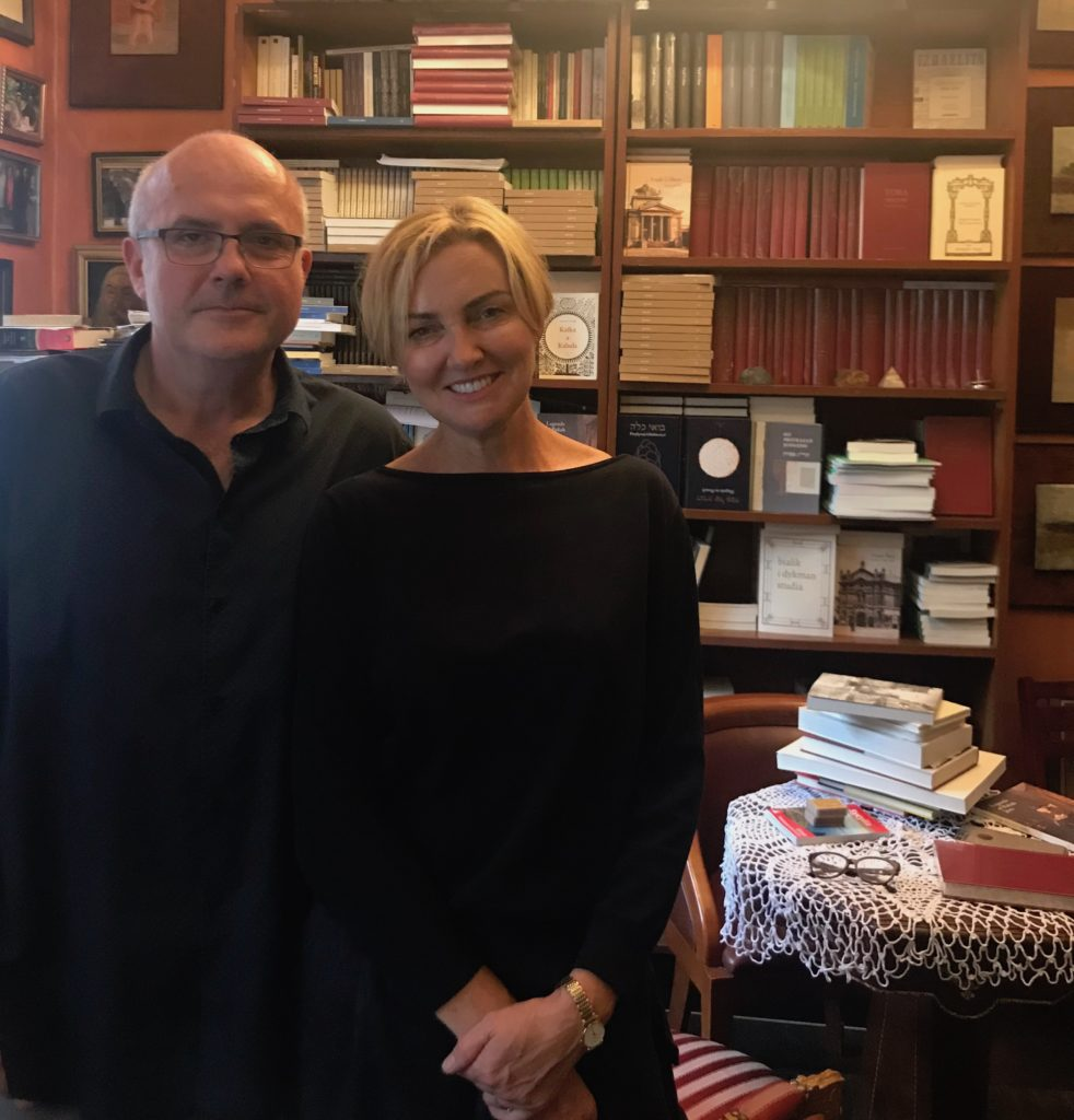 Photograph of a smiling couple in front of a bookcase.