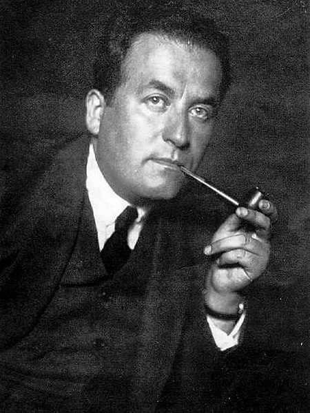 Black and white photo of a man smoking a pipe.