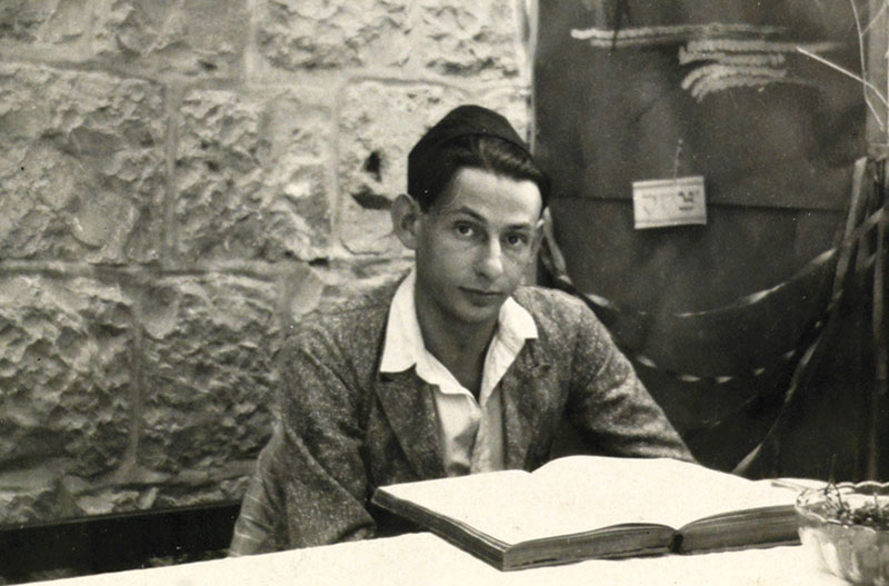 Young boy sitting in front of an open book