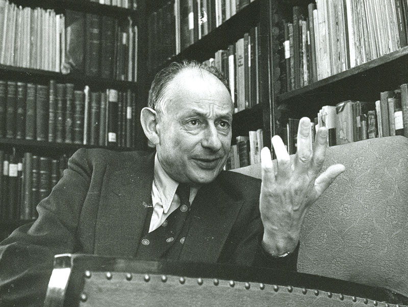 Gershom Scholem sitting in his apartment in front of bookshelves