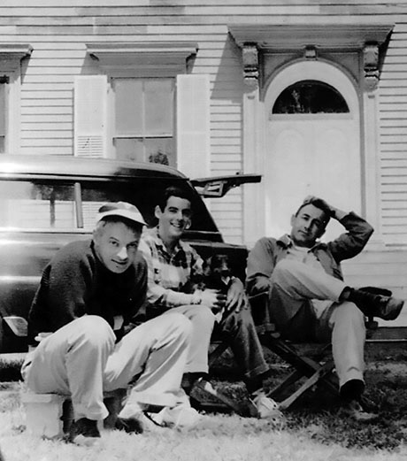 Black and white photo of three men sitting in front of a house