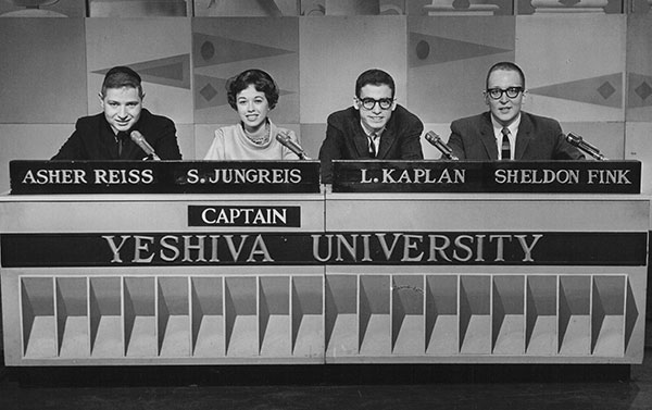Four students seated at a desk for a quiz show