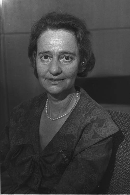 Black and white photograph of an older woman, wearing pearls, seated, looking at the camera.