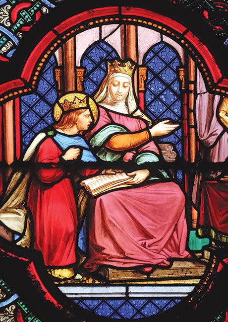 Stained glass picture of a crowned woman and a small child reading a book