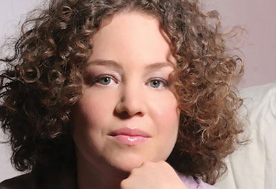 Headshot of a woman with curly hair