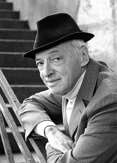 A black and white photo of an older gentleman in a fedora hat
