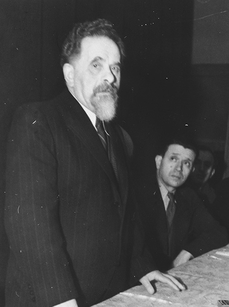 Black and white photo of a man standing in front of a table giving a speech