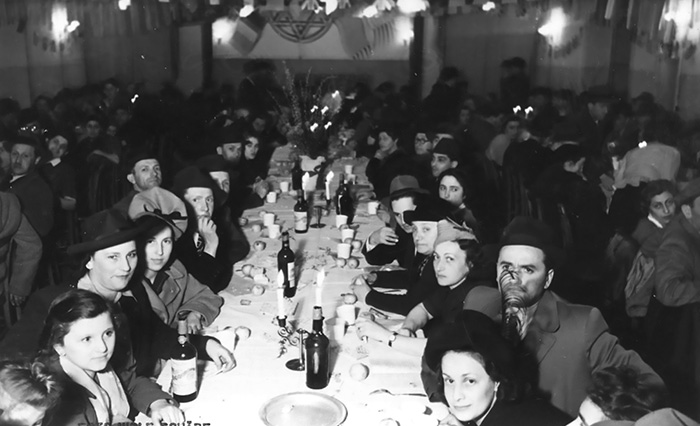 Black and white photo of men and women sitting at a long dinner table in a DP camp