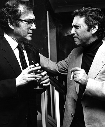 Black and white photo of two men smoking and talking to each other