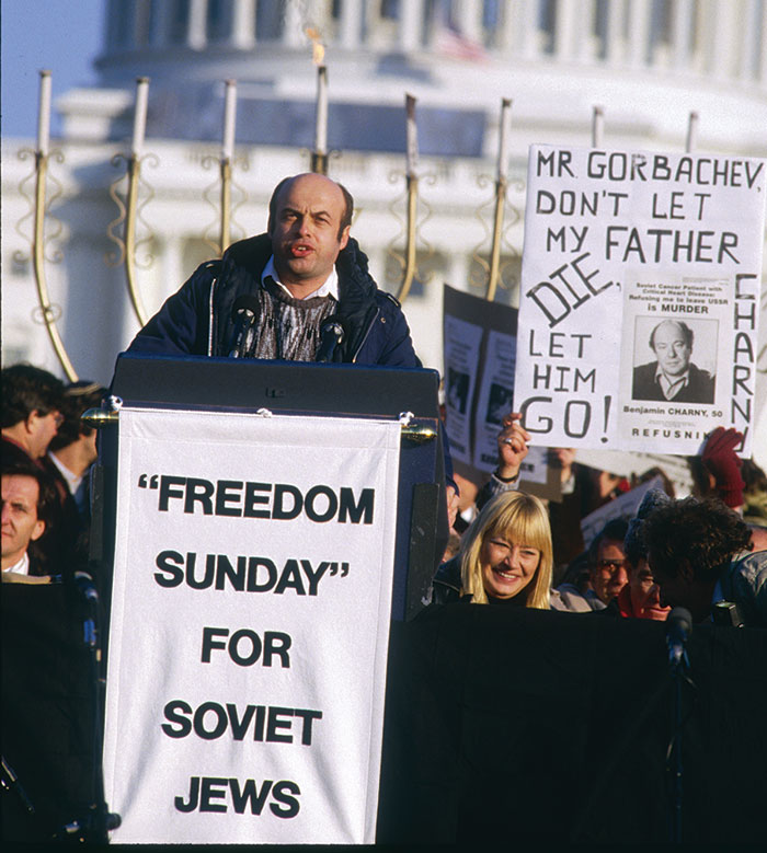 "Anatoly (Natan) Sharansky standing at podium with the sign ""Freedom Sunday"" for Soviet Jews written on it,"