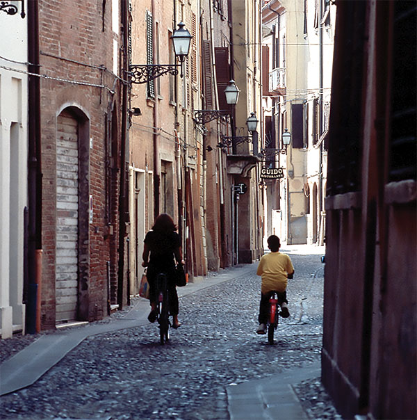 A view of the Jewish ghetto of Ferrara with two people on bicycles riding down a cobblestone street.
